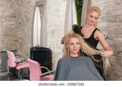 Stylist drying hair of female client at beauty salon. Young female beautician giving new hair style to woman at parlor