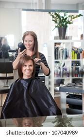 Stylist drying woman's hair in beauty salon .