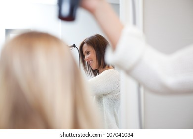 Stylist drying womans hair in beauty salon .