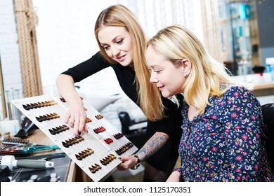 Stylist helps female client to choose hair dye color with hair swatches chart