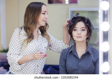 Stylist makeup artist doing makeup and hair in a beauty salon. Professional make-up, master of image creation