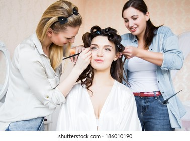 Stylist and makeup artist preparing bride before the wedding in a morning