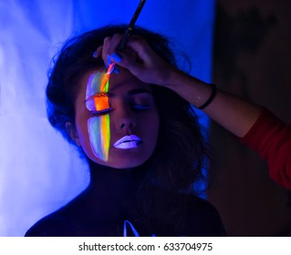 stylist making fluorescent glowing Body Art make-up to sexy fashion model in uv neon light with . Low key dark image. Soft focus image.