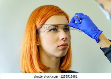 Stylist measuring the eyebrows with the ruler on a red-haired woman over the white background. Micropigmentation work flow in a beauty salon.