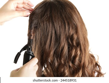 Stylist using curling iron for hair curls, close-up, isolated on white