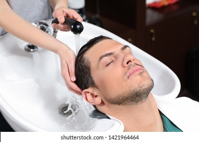Stylist washing client's hair at sink in beauty salon