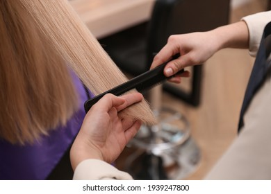 Stylist working with client in salon, closeup. Making haircut