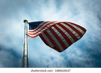 Stylized American flag flying on pole with cloudy blue sky background.