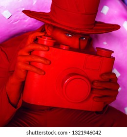 Stylized fantasy red photographer in scenic make-up with camera.