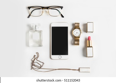 Stylized feminine flatlay with glasses, lipstick, perfume, watch, pendant  and smart phone mock up isolated on white top view. Woman accessories from above copy space for text.