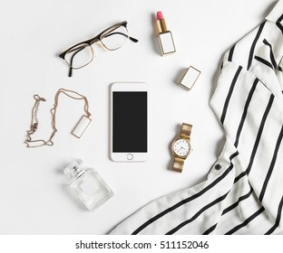 Stylized feminine flatlay with glasses, lipstick, perfume, watch, pendant, striped shirt  and smart phone mock up isolated on white top view. Woman accessories from above copy space for text.