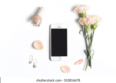 Stylized feminine flatlay with nail polish, flowers, petals, ribbon and smart phone mock up isolated on white top view. Woman accessories from above