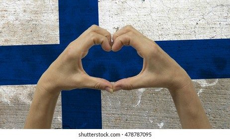 With a stylized Finnish flag background an anonymous person's hands being held in the form of a heart, symbolizing love and patriotism for Finland.