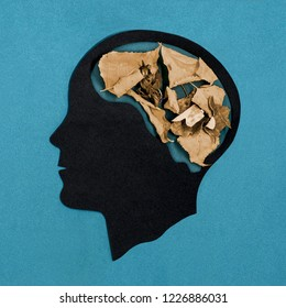 Stylized head silhouette. Brain is filled with dry twisted leaves. Symbol of dementia, brain aging, memory loss. Concept of mental health and disease