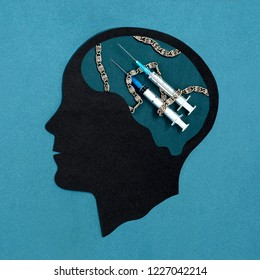 Stylized head silhouette. Brain with syringes and chain. Symbol of drug addiction. Concept of mental health and disease