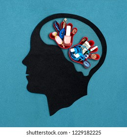 Stylized head silhouette. Palms with different objects in brain. Symbolic image of kleptomania, painful desire to steal. Concept of mental health and disease