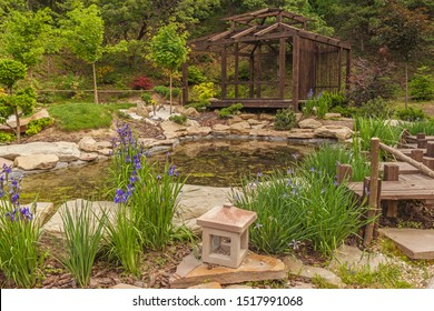 Stylized Japanese garden with blooming Siberian irises and oriental lantern on the background of the tea pavilion in spring