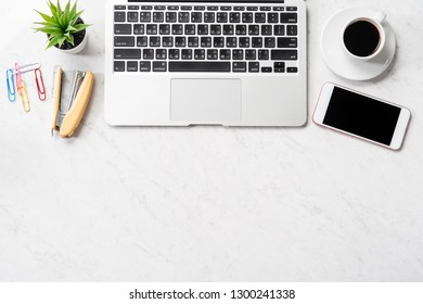 Stylized marble office working desk with smartphone, laptop, glasses and coffee, workspace design, mock up, topview, flat lay, copyspace, closeup