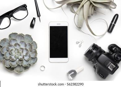 Stylized photo. Minimal flatlay with smartphone, candle, camera, ring, lipstick, nail polish, eyeliner, earrings and succulent plants on white background. Feminine workspace desktop top view. Mock up
