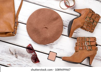 Stylized set of female fashion outfit. Stylish women brown boots and accessories on white wooden background. Flat lay feminine modern attire.