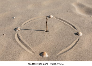 Stylized for a sundial. Wand, sun and sea shells in the sand