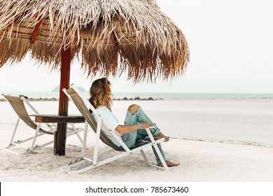 styllish young beautiful woman in casual wear relaxing in chair on the tropical beach