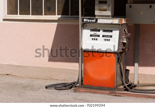 STYRIA, AUSTRIA - AUGUST 2017: Old diesel pump. Filling station in front of pink colored house. Detailed warnings in German for safe refueling: stop engine, no open fire, no smoking, no spillage.