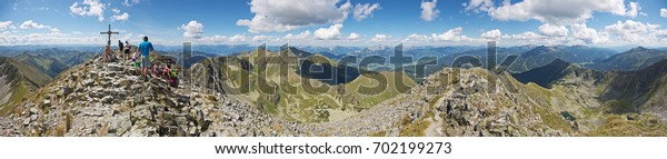 STYRIA, AUSTRIA - AUGUST 2017: Panoramic view from rocky mountain peak Boesenstein, Lower Tauern. Hikers enjoying fantastic clear views over the high alpine landscape under cloudy blue sky in summer.