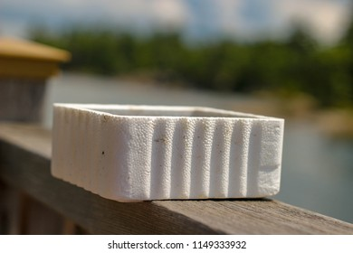 A styrofoam bait worm container on a ledge next to a lake ready to be used for fishing. blurred background and isolated object with room for copy space