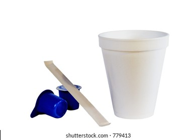 Styrofoam coffee cup, creamers, and stir stick isolated on white.
