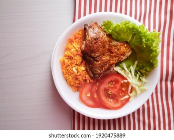 Styrofoam lunch box with roasted chicken and salad and farofa on the table and towel and with space for text
