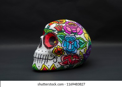 Styrofoam skull hand painted, decorated with mexican flowers against black background