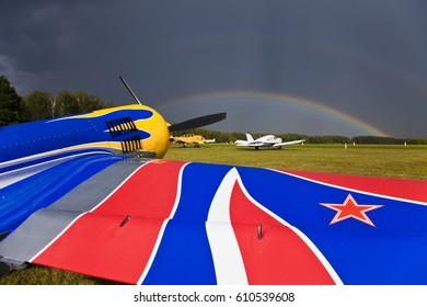 SU-26 sport airplane on the airfield. Rainbow over the sky.