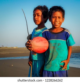 Suai Loro, Timor-Leste - September 29 2015. Unidentified Timorese children taking a break for a chat while learning to play football on the beach.