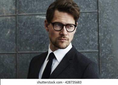 Suave man in spectacles and suit, looking away