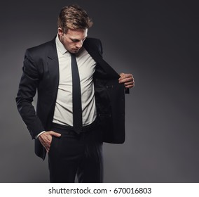 Suave young businessman checking out the jacket of a stylish black suit standing alone in a studio against a grey background
