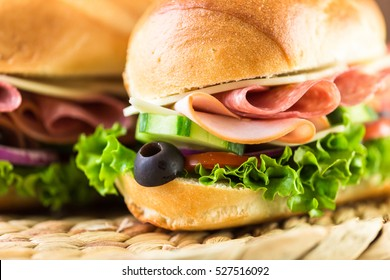 Sub sandwich with fresh vegetables, lunch meat and cheese on hoagie roll.