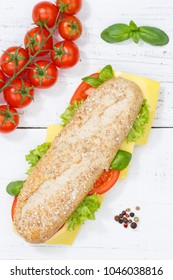 Sub sandwich whole grain grains baguette with cheese from above portrait format on wooden board wood