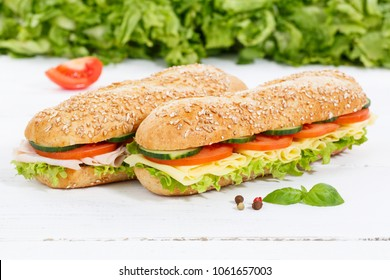 Sub sandwiches whole grain grains baguettes with ham and cheese on wooden board wood