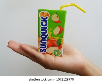 Subang Jaya , Malaysia - 15 April 2018 : Hand hold a box packet of Sunquick liquid flavor Apple over white background. Sunquick is a product of CO-RO A/S a Danish company.
