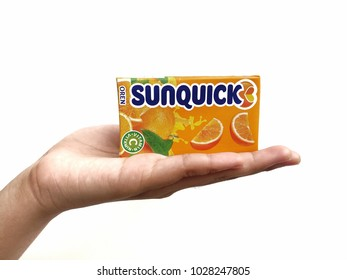 Subang Jaya , Malaysia - 15 February 2018 : Hand hold a box packet of Sunquick liquid flavor Orange isolated white background. Sunquick is a product of CO-RO A/S a Danish company.