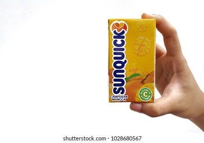 Subang Jaya , Malaysia - 15 February 2018 : Hand hold a box packet of Sunquick liquid flavor Mango over white background. Sunquick is a product of CO-RO A/S a Danish company.
