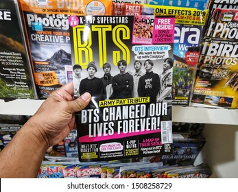 Subang Jaya, Malaysia - 15 September 2019 : Hand hold a K-POP SUPERSTARS BTS magazine for sell in the book stores with selective focus.