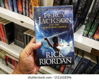 Subang Jaya, Malaysia - 15 September 2019 : Hand hold a RICK RIORDAN book title - PERCY JACKSON AND THE LIGHTING THIEF for sale at library book stores with selective focus.