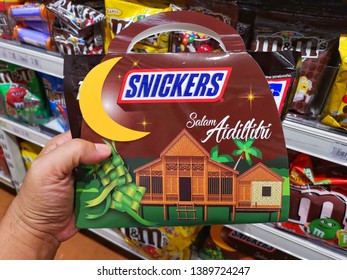 Subang Jaya, Malaysia - 30 April 2019 : Hand hold a packed of SNICKERS Chocolate Bar - Salam Aidilfitri for sell in the supermarket with selective focus.