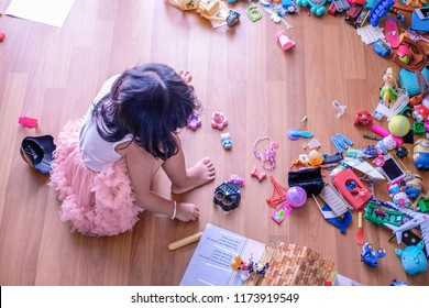 Subang Jaya, Malaysia - August 31, 2018 : Picture of little girl seating on wooden floor with her messy toys.