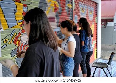 Subang Jaya, Malaysia - June 28, 2019: A group of friends team up volunteering time & effort painting colorful street artwork on a store front, brightening up the community area with a fresh new look.
