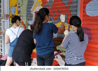 Subang Jaya, Malaysia - June 28, 2019: A beautiful street art takes shape as a volunteer group of young girls work together painting a store front to bring a new breath of life to the community area.