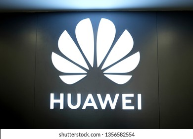 Subang Jaya, Malaysia - March 28, 2019: Huawei Technologies corporate logo and name lighted up on a wall in a store selling Huawei products.