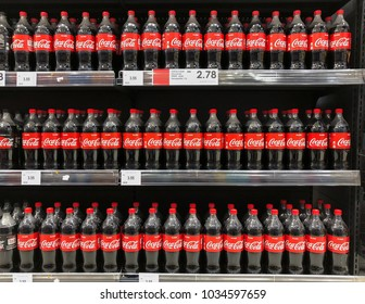 SUBANG, MALAYSIA - FEBRUARY 23, 2018: Coke in bottles on row of shelf display for sale in hypermarket grocery store. Coca-Cola, or Coke, is a carbonated soft drink produced by The Coca-Cola Company.
